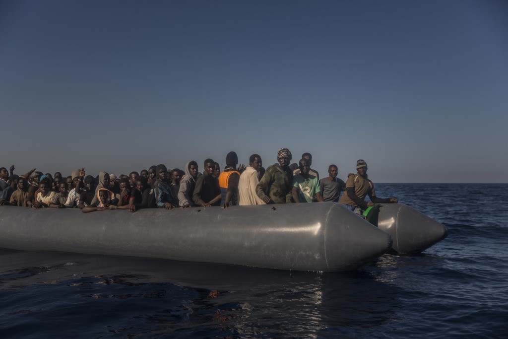 Refugees and migrants from different African countries wait to be assisted by an NGO aboard an overcrowded rubber boat, about 20 miles ...