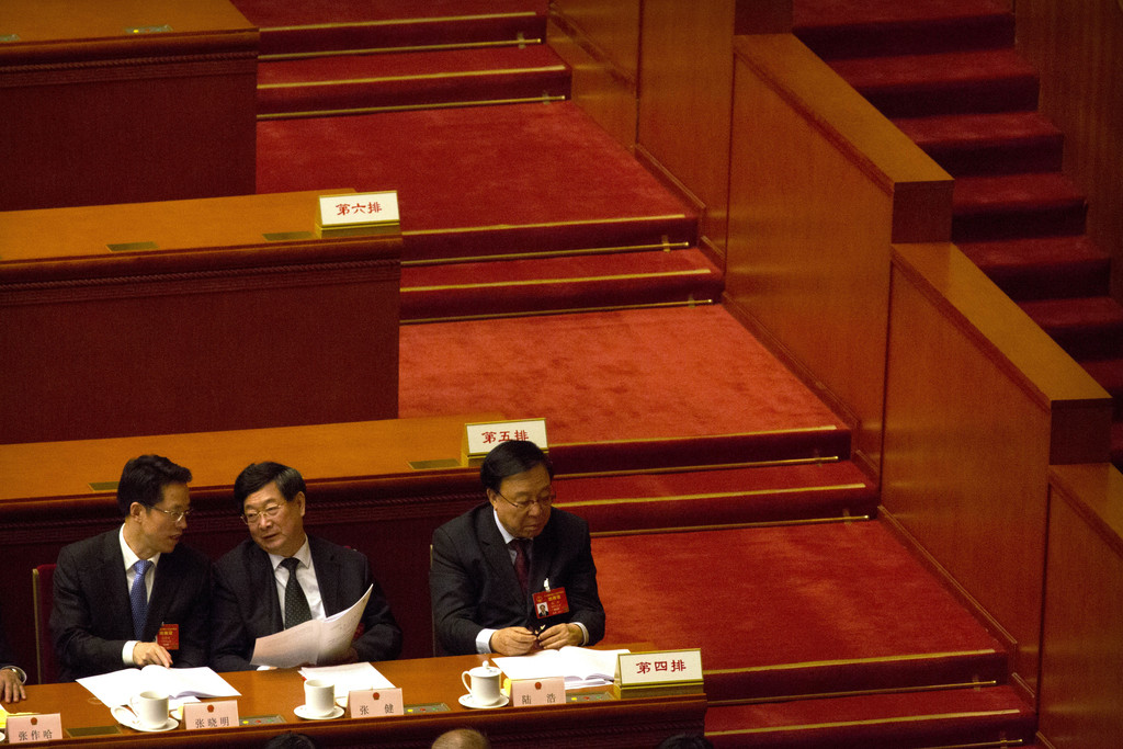 Delegates talk amongst themselves during the opening session of China's annual National People's Congress in Beijing's Great Hall of th...
