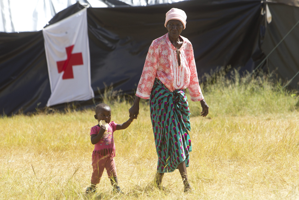 A woman and child walk, at a camp set up for flood victims in Tsholostho about 200 kilometres north of Bulawayo, Saturday, March 4, 201...