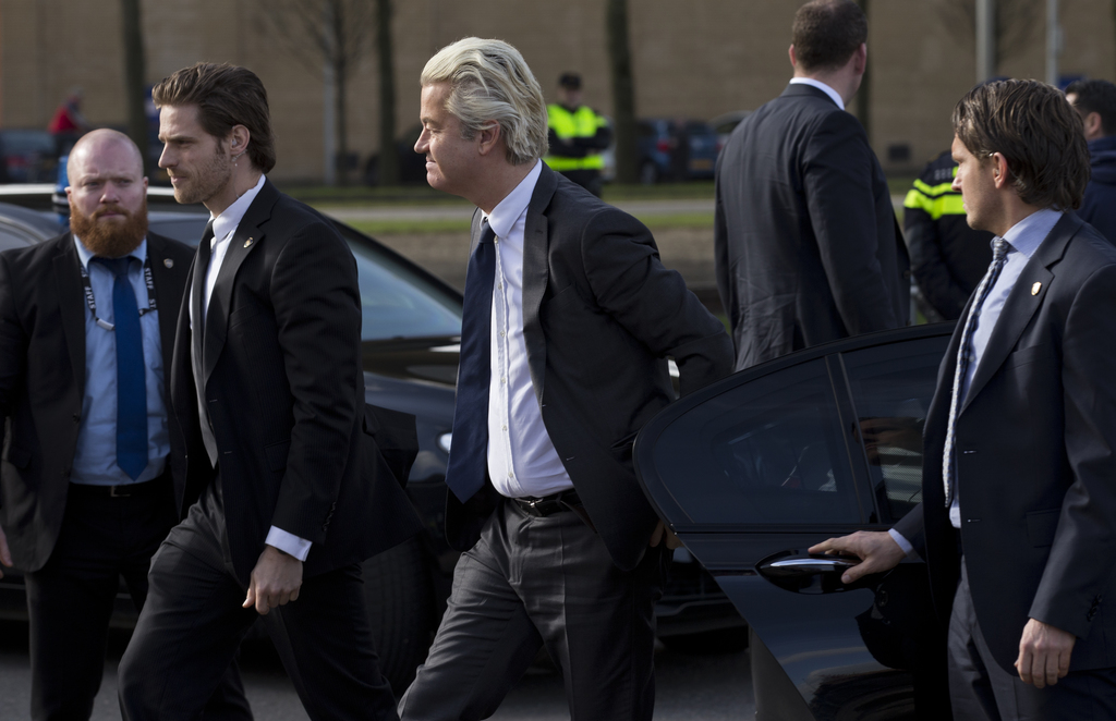 Firebrand anti Islam lawmaker Geert Wilders, center, is surrounded by body guards as he arrives for an election campaign stop outside D...