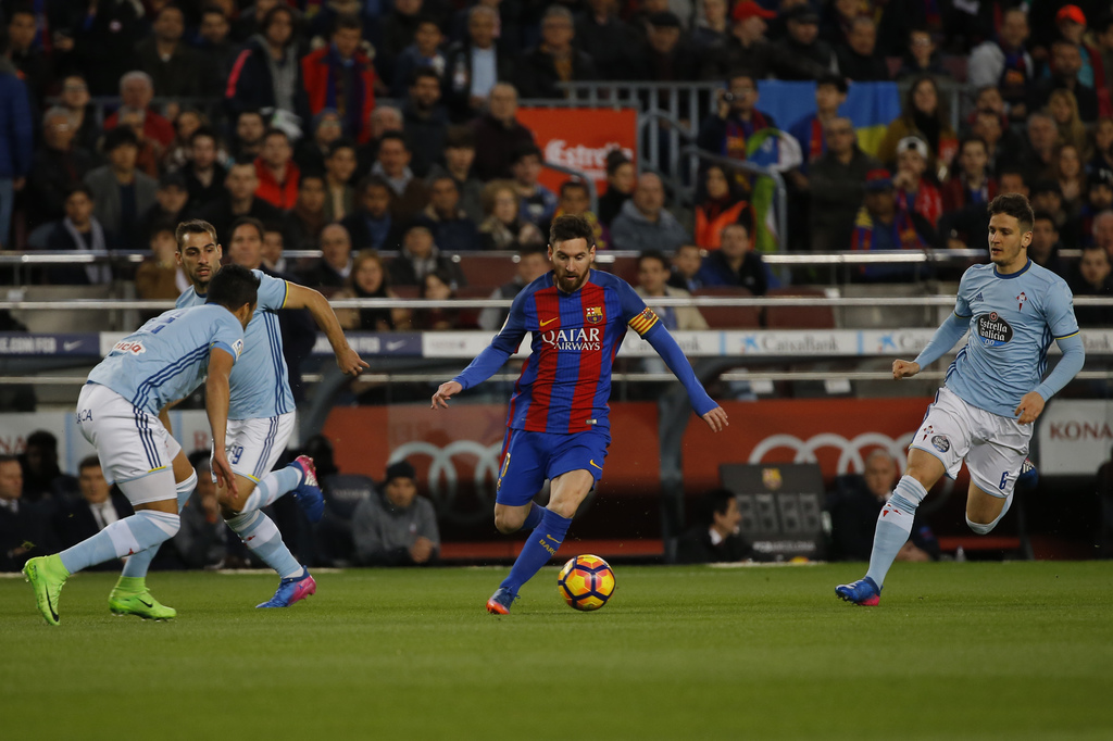 Barcelona's Lionel Messi, center, runs with the ball past Celta's defenders during a Spanish La Liga soccer match between Barcelona and...