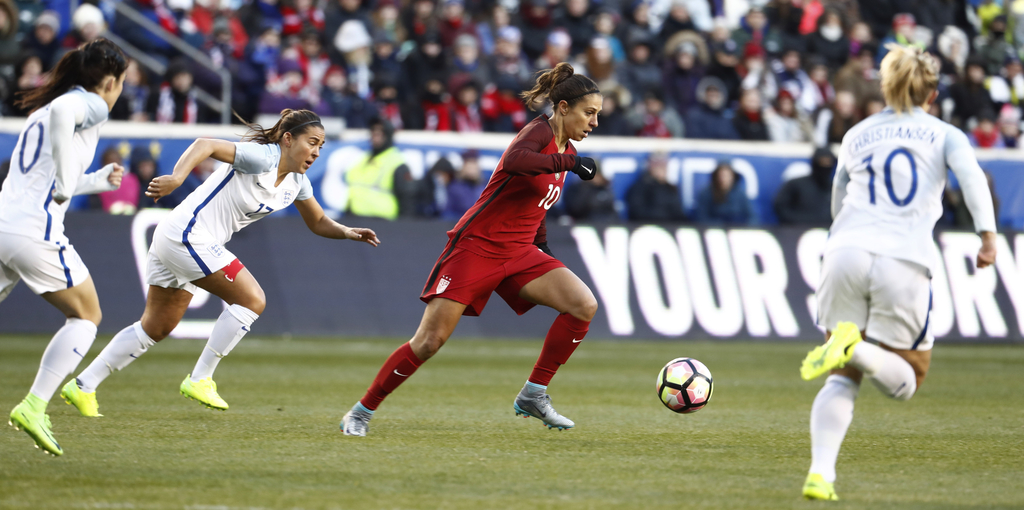 United States midfielder Carli Lloyd, center, moves the ball upfield against England during the first half of a SheBelieves Cup women's...