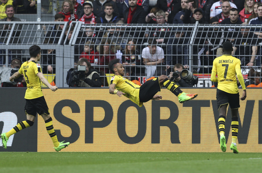 Dortmund's scorer Pierre-Emerick Aubameyang, center, celebrates with a somersault while Marc Bartra, left,  and Ousmane Dembele . right...