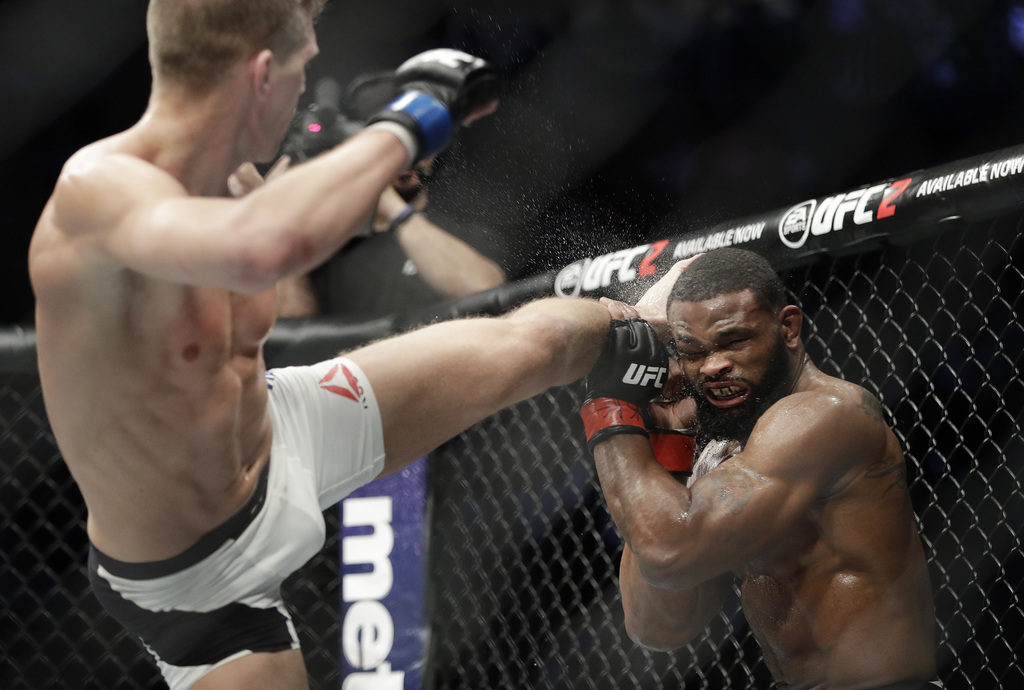 Stephen Thompson, left, kicks Tyron Woodley during a welterweight championship mixed martial arts bout at UFC 209, Saturday, March 4, 2...