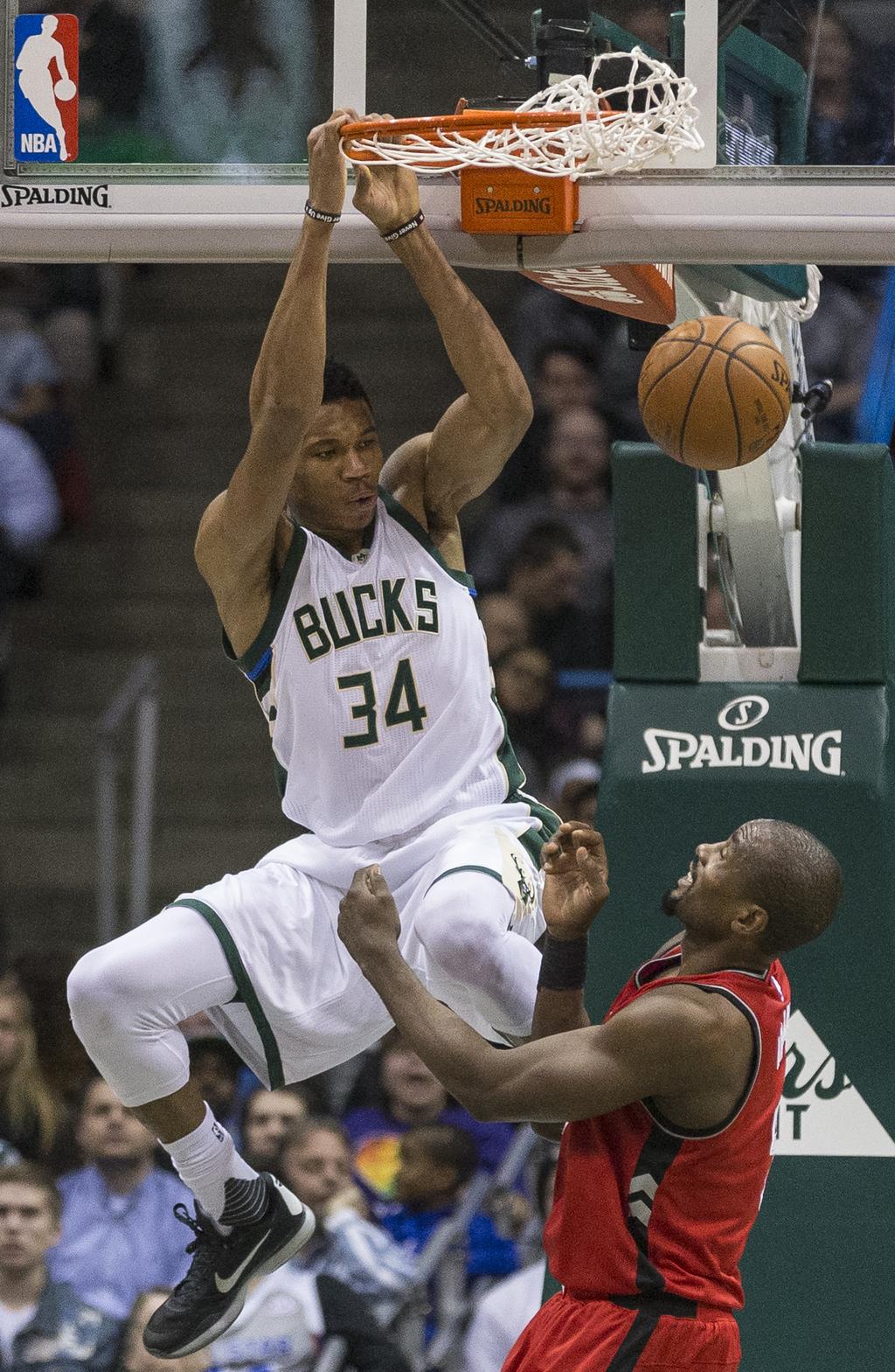 Milwaukee Bucks' Giannis Antetokounmpo dunks the ball as Toronto Raptors' Serge Ibaka looks on during the first half of an NBA basketba...