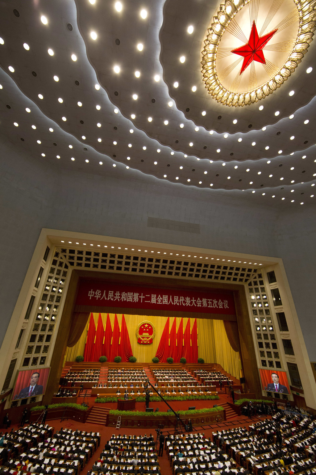 Chinese Premier Li Keqiang is displayed on huge screens as he delivers a work report at the opening session of the annual National Peop...
