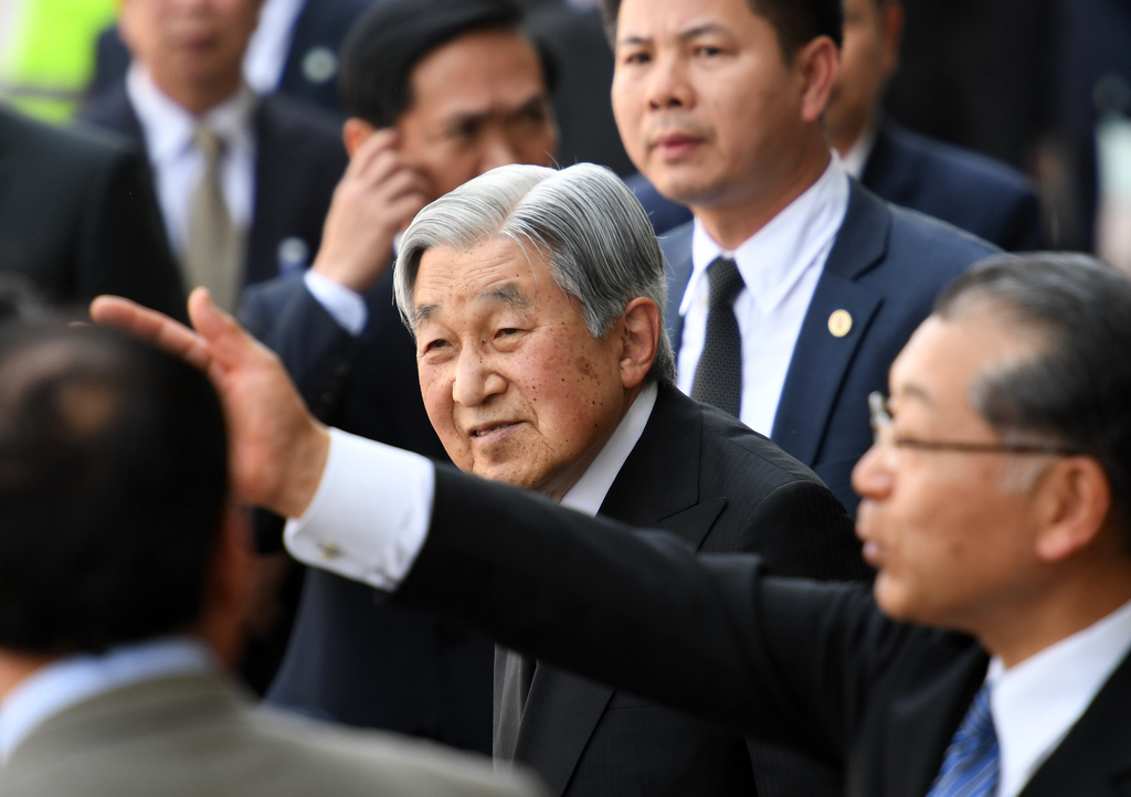 Japan's Emperor Akihito, center, is flanked by security men on his arrive at the Phu Bai airport in the central city of Hue, Vietnam as...