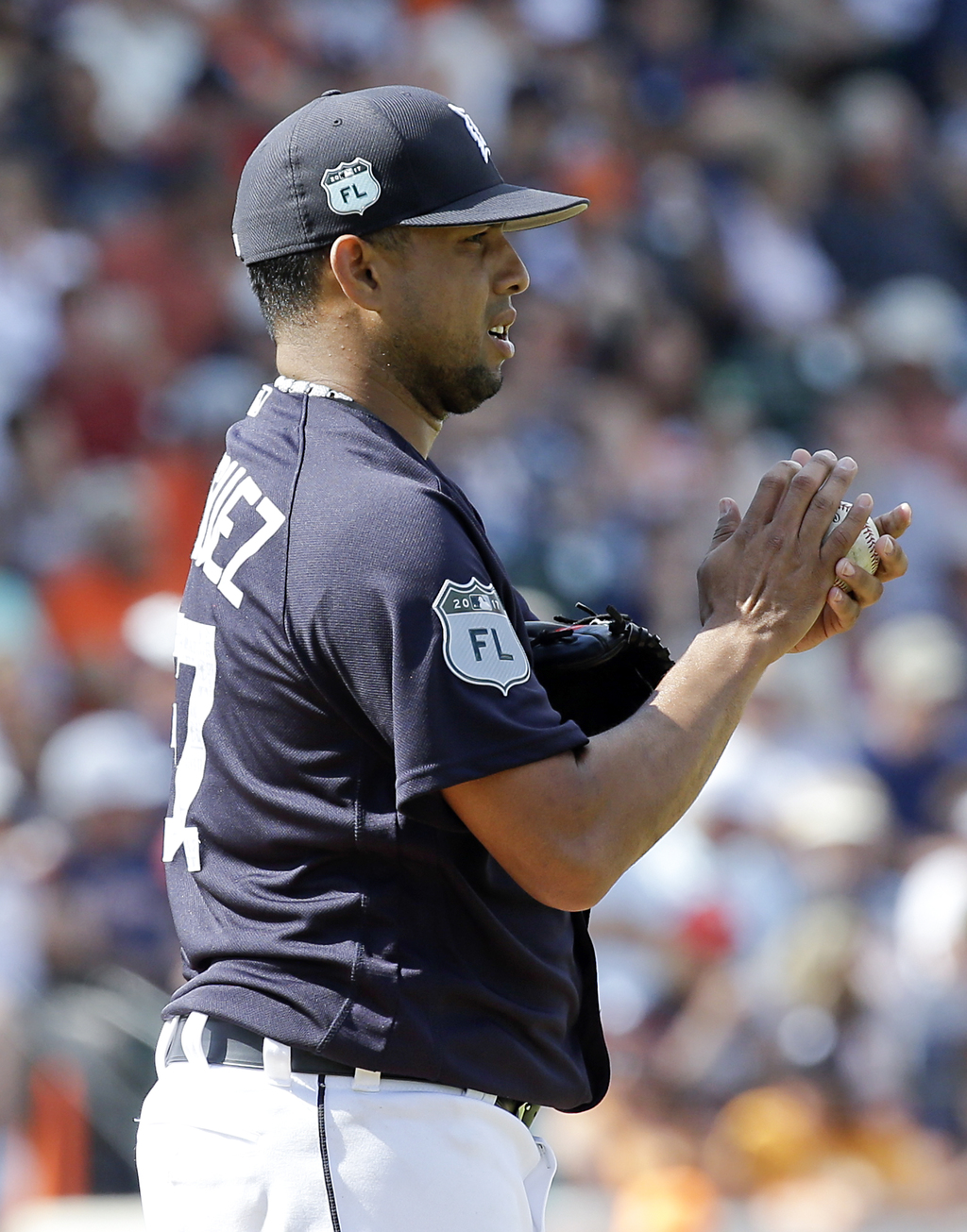Detroit Tigers relief pitcher Francisco Rodriguez rubs the ball with his hands before throwing a pitch against the New York Yankees in ...