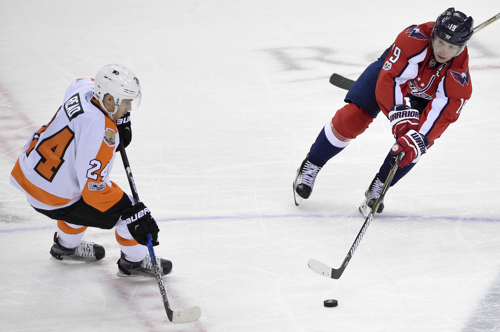 Washington Capitals center Nicklas Backstrom (19), of Sweden, reaches for the puck against Philadelphia Flyers right wing Matt Read (24...