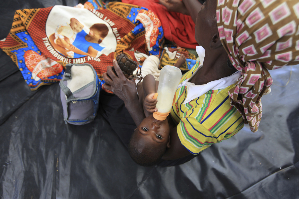A woman feeds her baby inside a camp set up for flood victims in Tsholostho about 200 kilometres north of Bulawayo, Saturday, March 4, ...