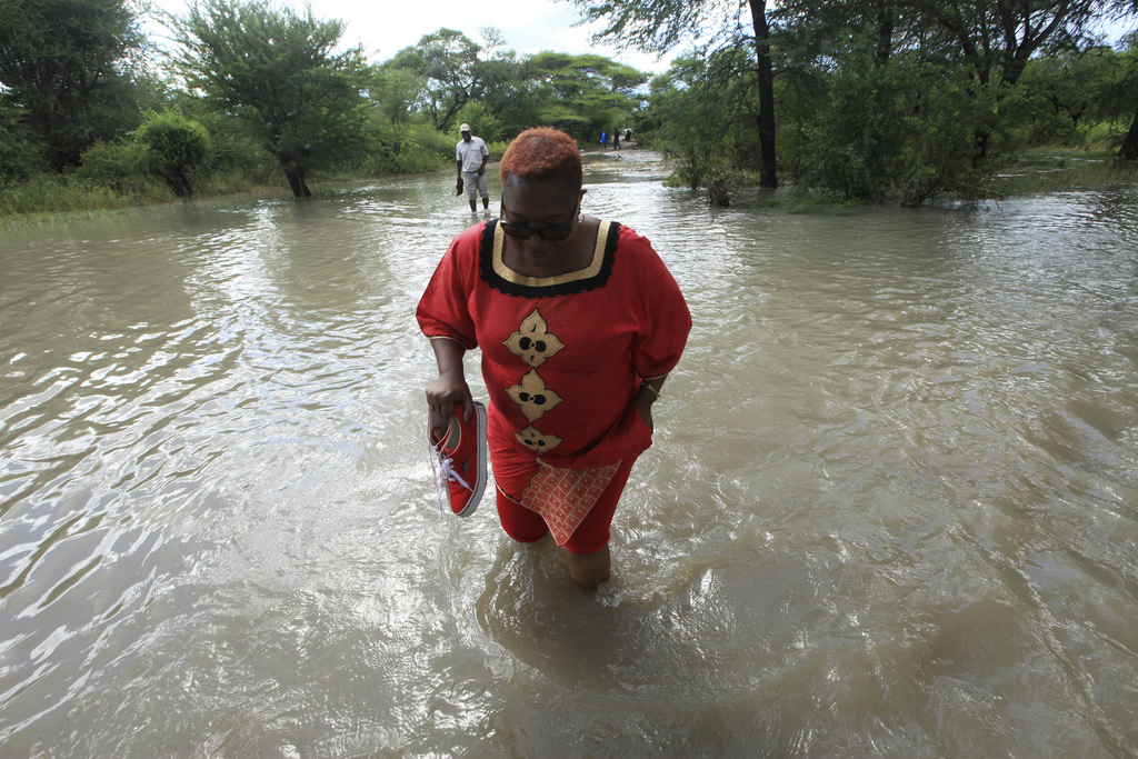 Former Zimbabwean Deputy Prime Minister Thokozani Khupe crosses a flooded road on her way to assess damages caused by floods in Tsholos...