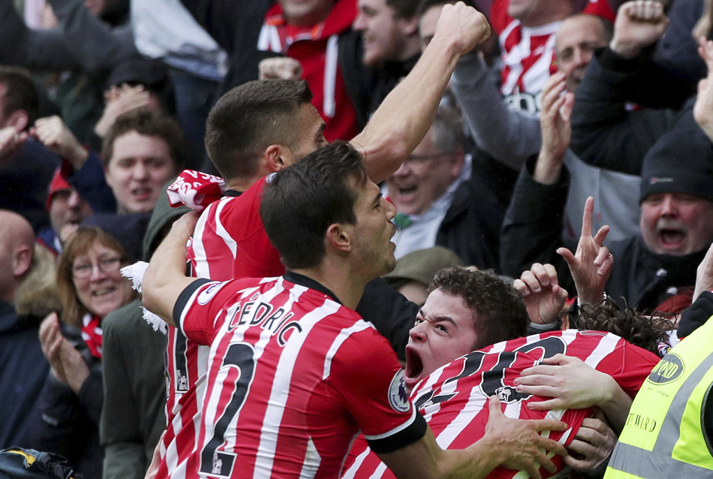 Southampton's Manolo Gabbiadini celebrates with teammates and fans after scoring his side's third goal, during the English Premier Leag...