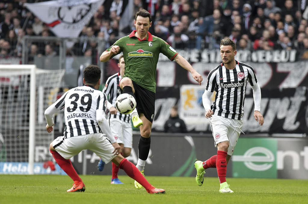 Frankfurt's  Omar Mascarell, left, and Danny Blum, right, challenge for the ball with Freiburg's  Nicolas Hoefler , center, during a Ge...