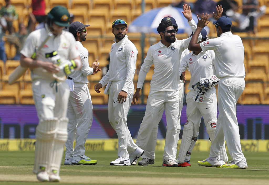 India's Ravindra Jadeja, center without a cap, celebrates with teammates the dismissal of Australia's captain Steven Smith, left, durin...