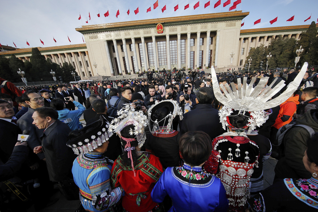 Minority delegates are surrounded by photographers as they arrive at the Great Hall of the People to attend the opening session of the ...
