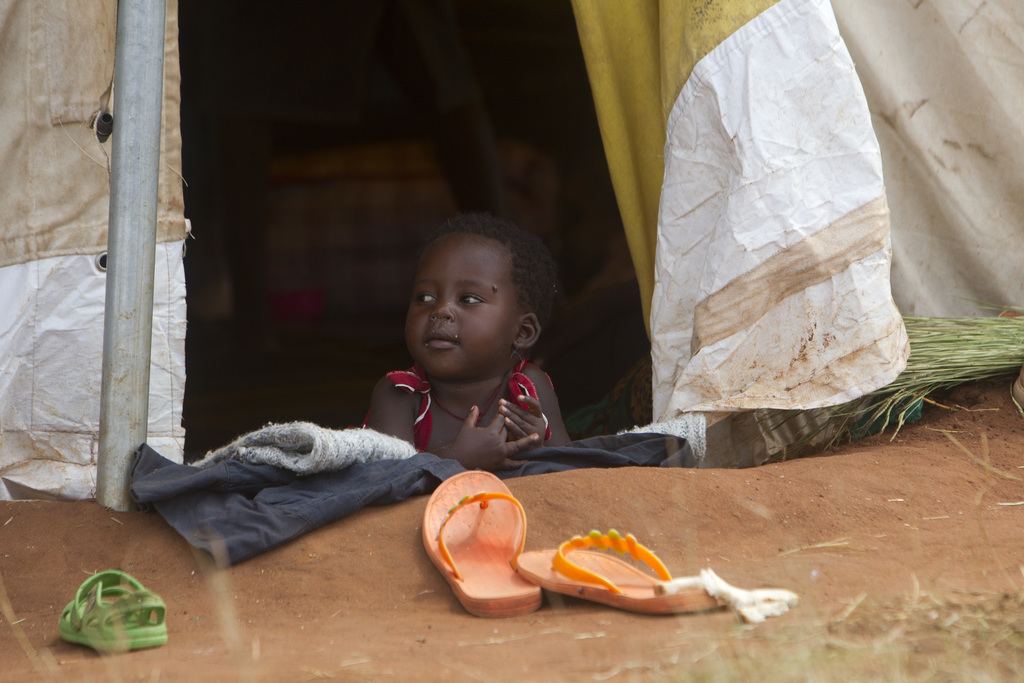 A child looks out of a shelter in a camp set up for flood victims in Tsholostho about 200 kilometres north of Bulawayo, Saturday, March...