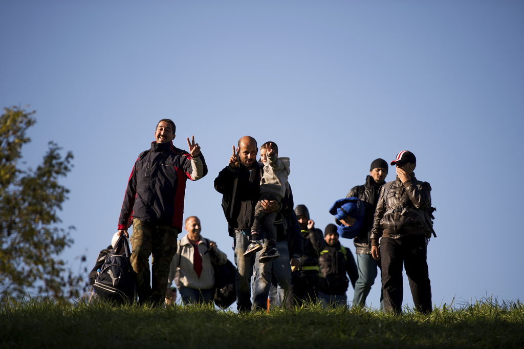 FILE - In this Oct. 20, 2015 file photo migrants cross the Austrian - Slovenian border in Spielfeld, Austria. Austria was among the fir...