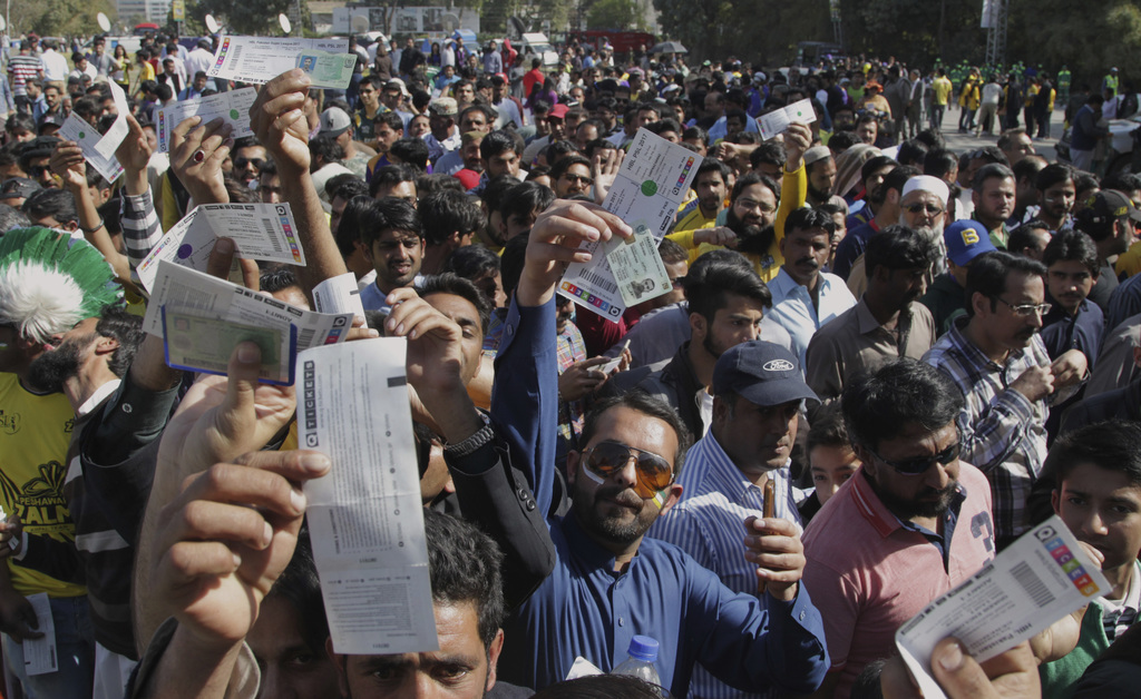 Cricket lovers raise their ticket while they waiting for security check to enter in the Gaddafi stadium in Lahore, Pakistan, Sunday, Ma...