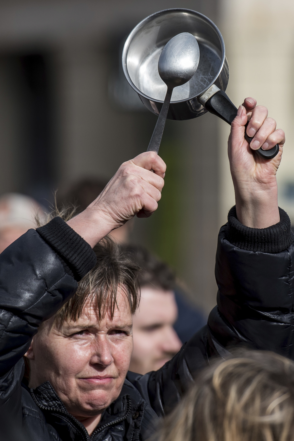 An activist beats with spoon on saucepan during an anti corruption rally in Paris, Sunday, March 5, 2017 while France's presidential ca...