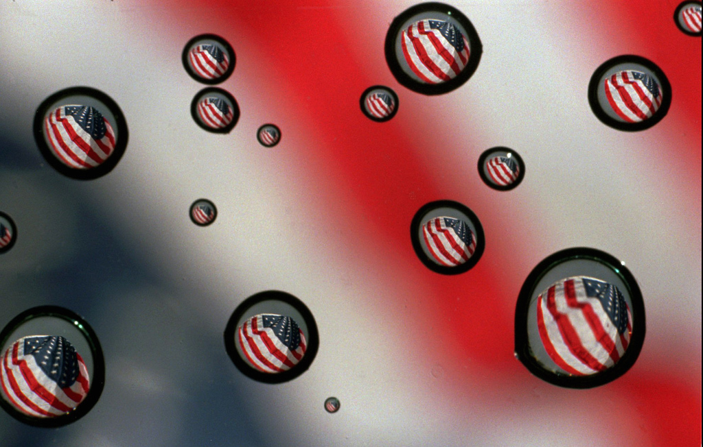 In this Nov. 10, 1997 file photo,a  U.S. flag refracted in water drops on a car windshield in Gorham, Maine. The vast majority of Ameri...