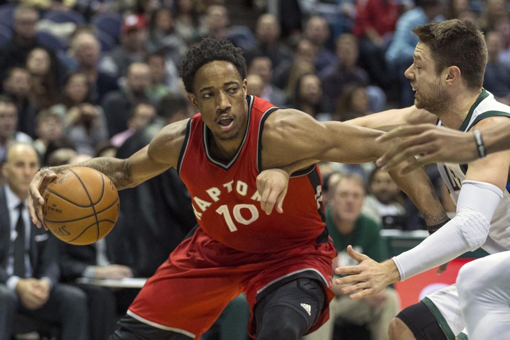 Toronto Raptors' DeMarre DeRozan drives against Milwaukee Bucks' Matthew Dellavedova during the first half of an NBA basketball game Sa...