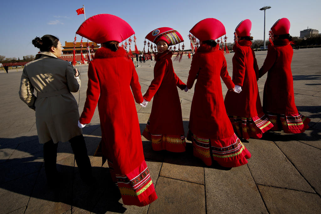 Bus ushers in ethnic minority costumes walk on Tiananmen Square during the opening session of the annual National People's Congress in ...