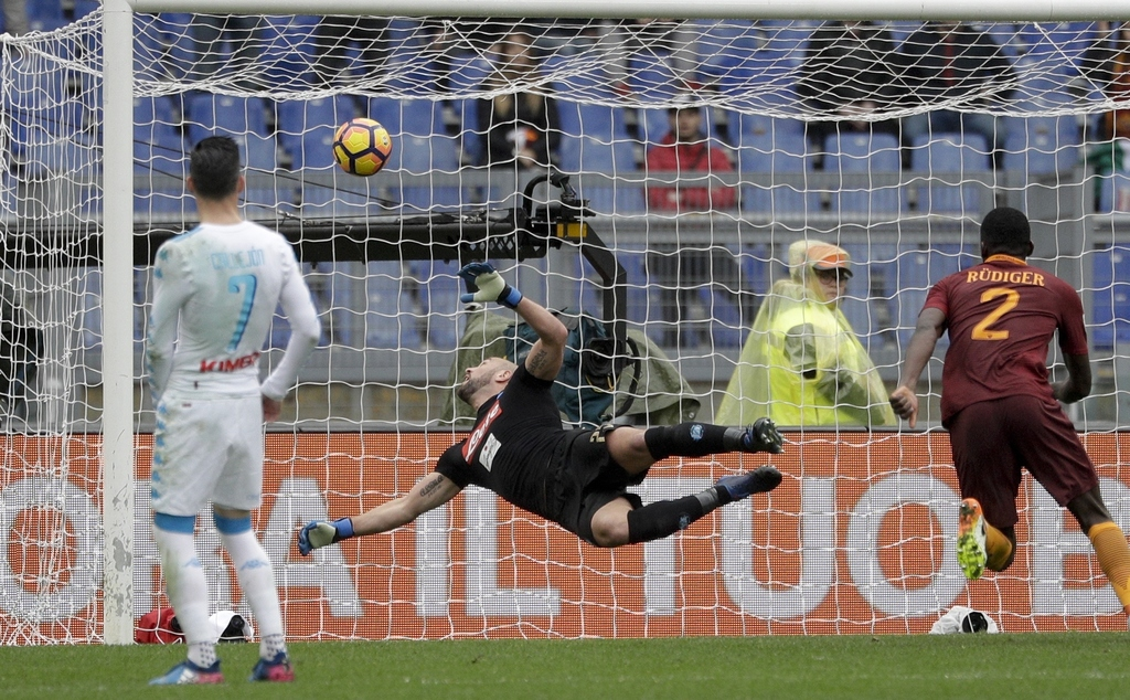Napoli goalkeeper Pepe Reina is airborne as he saves a shot during a Serie A soccer match between Roma and Napoli, at the Rome Olympic ...