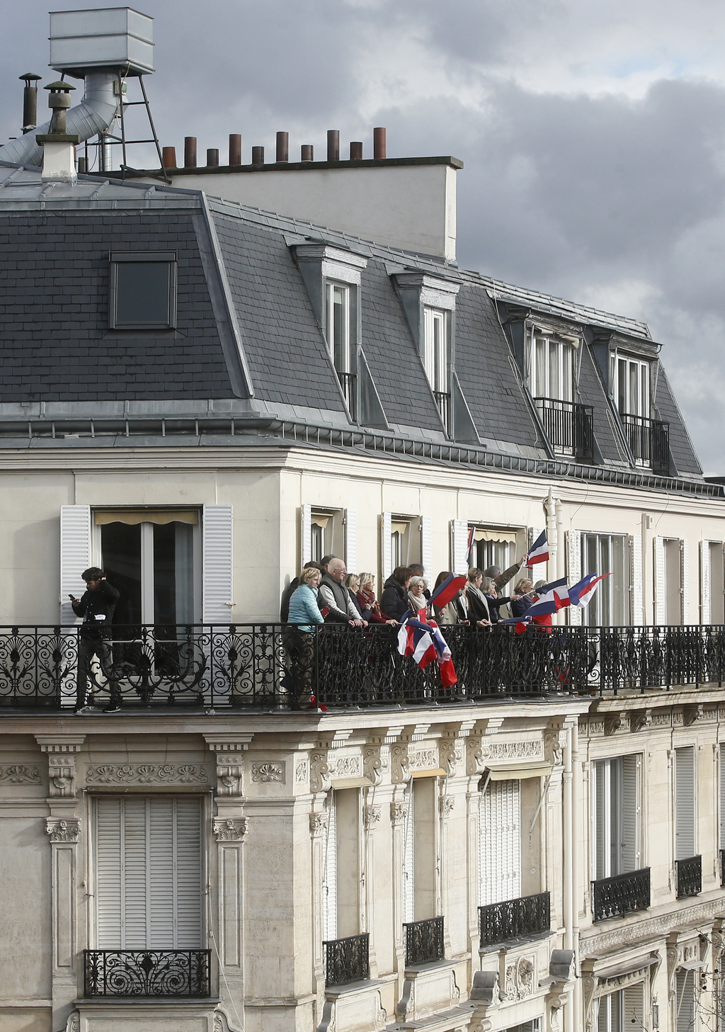 Supporters of conservative presidential candidate Francois Fillon wave French flags from a balcony overlooking a rally in Paris, Sunday...