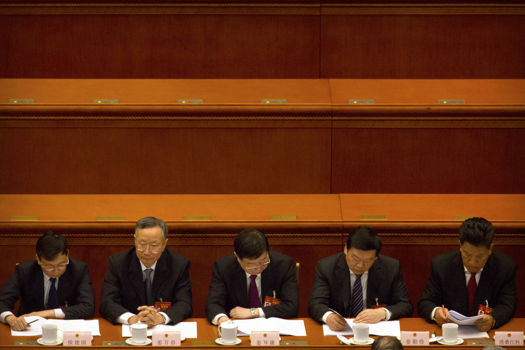 Delegates look at paperwork during the opening session of China's annual National People's Congress in Beijing's Great Hall of the Peop...