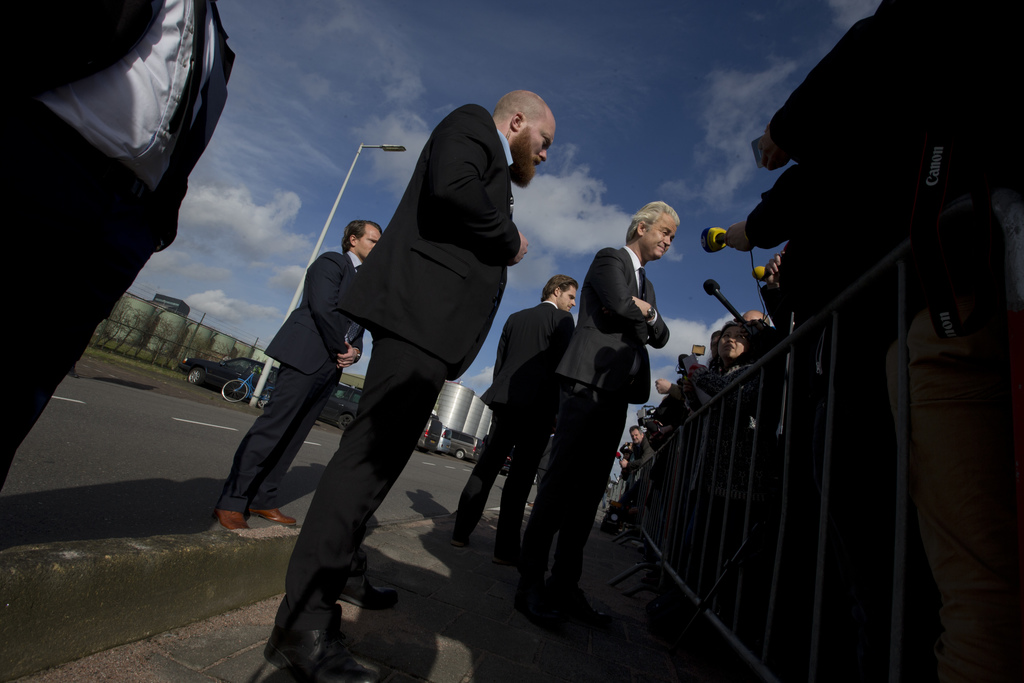 Security guards watch over firebrand anti Islam lawmaker Geert Wilders, center right, as he answers questions during an election campai...