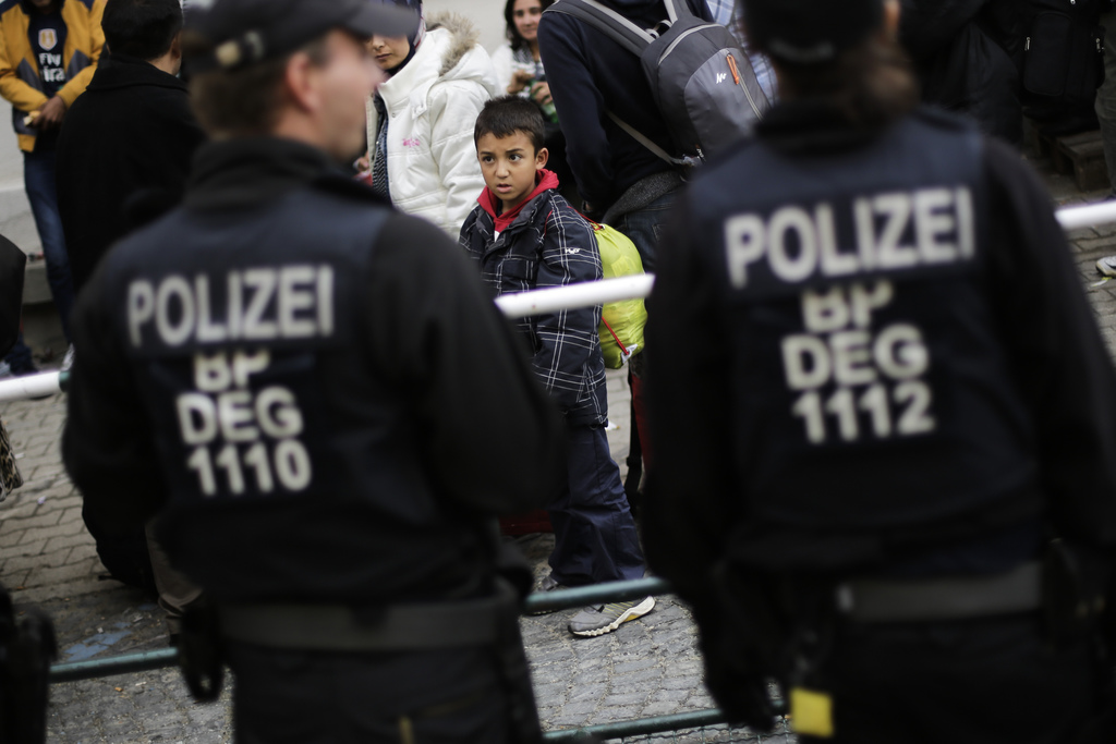 FILE - In this Sept. 16, 2015 file photo, a young boy looks at police officers after he and other migrants were pulled out of a train b...