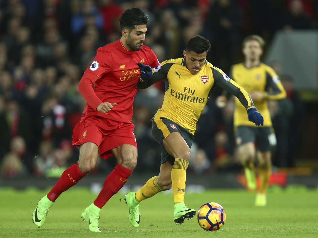 Arsenal's Alexis Sanchez, right, holds off the challenge of Liverpool's Emre Can during the English Premier League soccer match between...