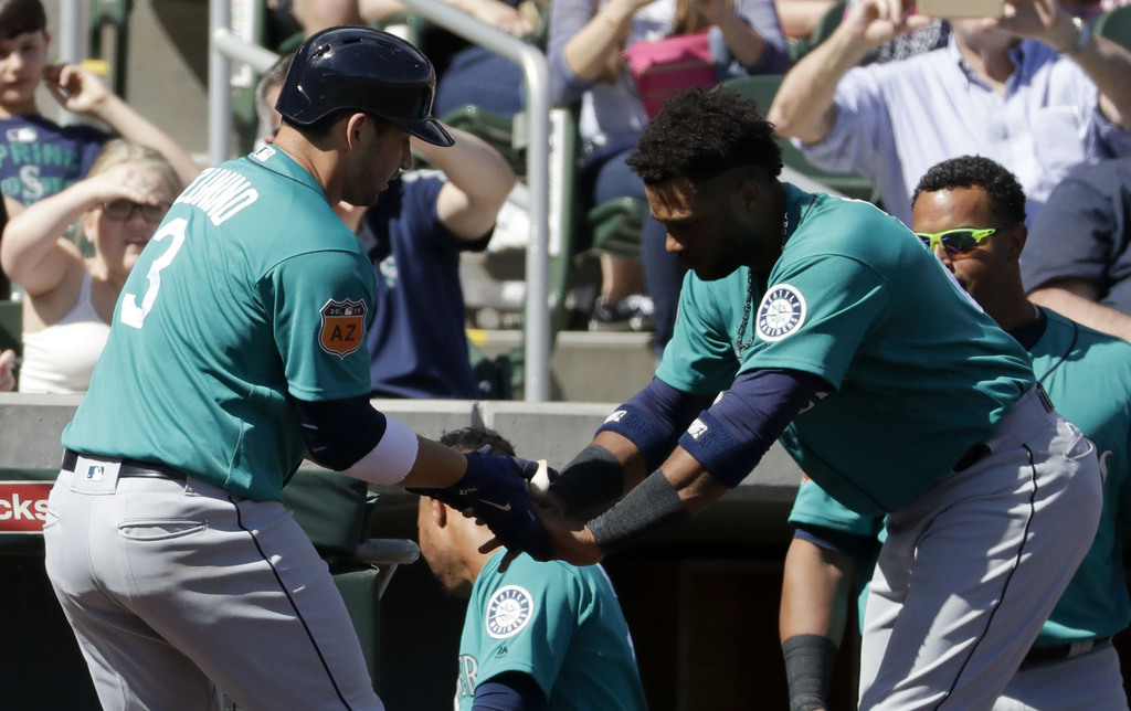 Seattle Mariners' Mike Zunino, left, celebrates after a home run with Robinson Cano during second inning at a spring baseball game agai...