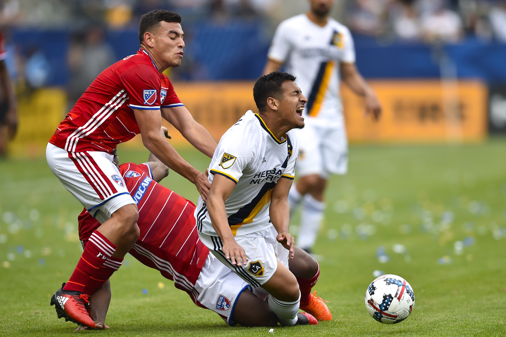 Los Angeles Galaxy midfielder Jose Villarreal, right, reacts as he gets tripped up by FC Dallas defender Maynor Figueroa, back center, ...