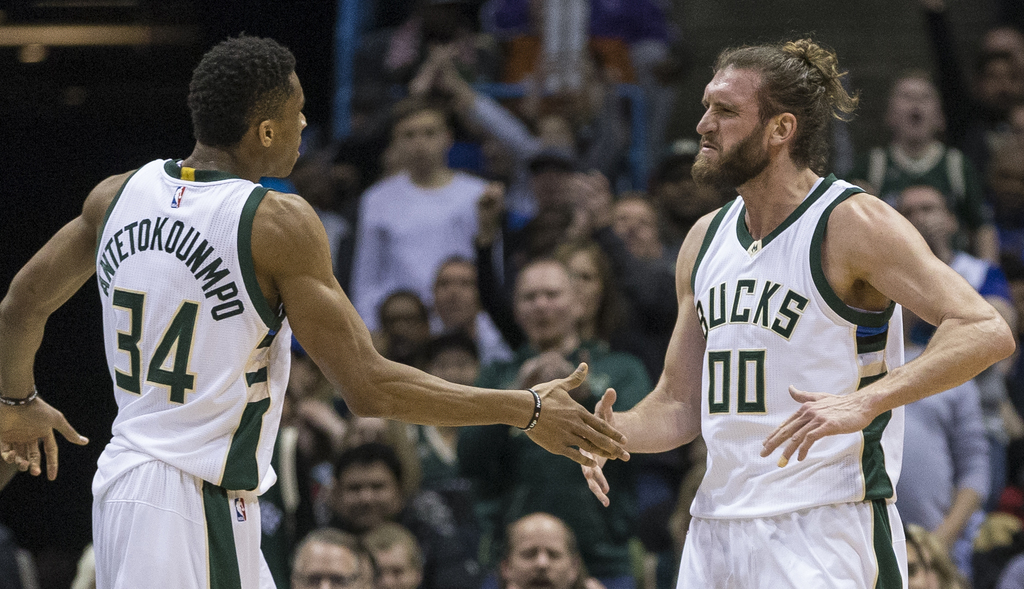 Milwaukee Bucks' Giannis Antetokounmpo, left, slaps hands with teammate Spencer Hawes after Hawes made a basket against the Toronto Rap...