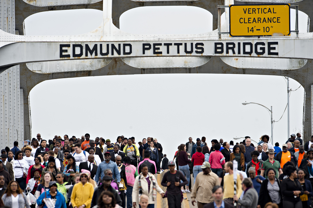 People walk over the Edmund Pettus Bridge towards Selma, Ala., during the annual re-enactment of a key event in the civil rights moveme...