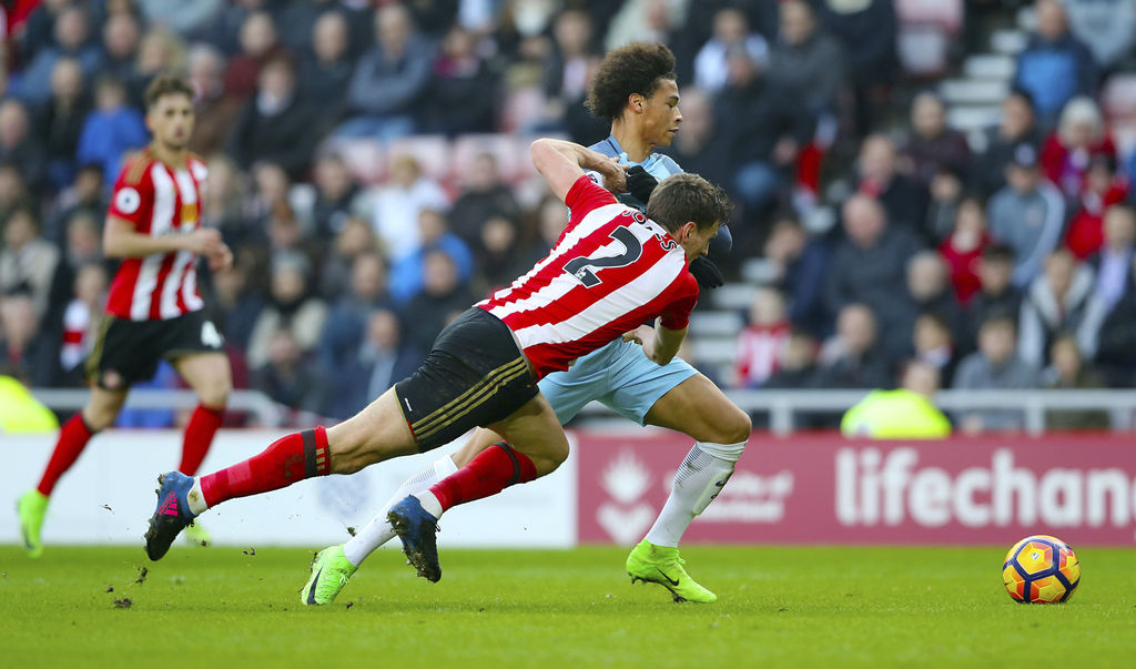 Sunderland's Billy Jones, left, and Manchester City's Leroy Sane battle for the ball during the Premier League soccer match between Sun...