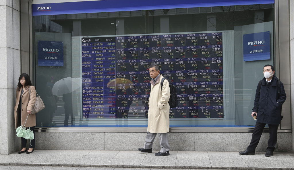 People shelter from the rain in front of an electronic stock board of a securities firm in Tokyo, Monday, March 6, 2017. Shares were mi...