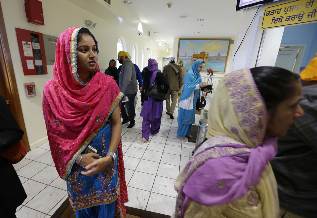 Satwinder Kaur, left, watches as people arrive for Sunday services at the Gurudwara Singh Sabha of Washington, a Sikh temple in Renton,...