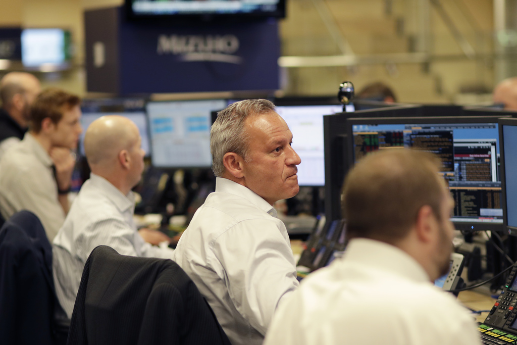 In this Jan. 12, 2017, photo, traders work on the Mizuho Americas trading floor in New York. Stocks are opening lower on Wall Street, M...