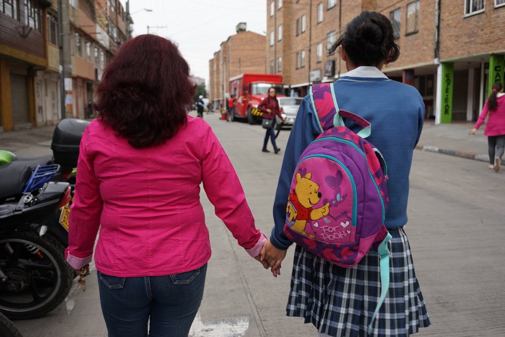 In this March 1, 2017 photo, Alba Diaz walks hand-in-hand with her granddaughter Nikol Hilarion through their neighborhood in Bogota, C...