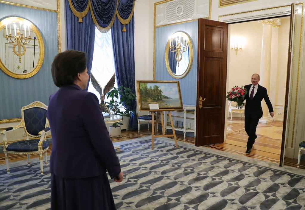 Russian President Vladimir Putin, right, carries flowers to congratulate the first woman in space, cosmonaut Valentina Tereshkova, on h...