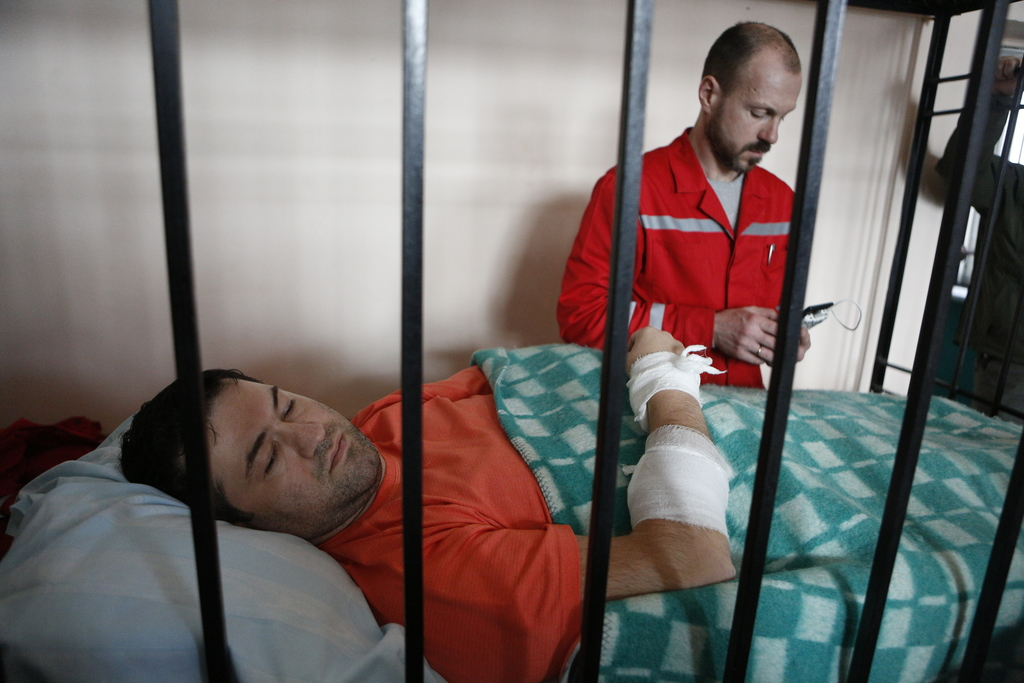 Head of Ukraine's State Fiscal Service Roman Nasirov, lays in a bed behind the bars with a medical worker in the background, during a c...