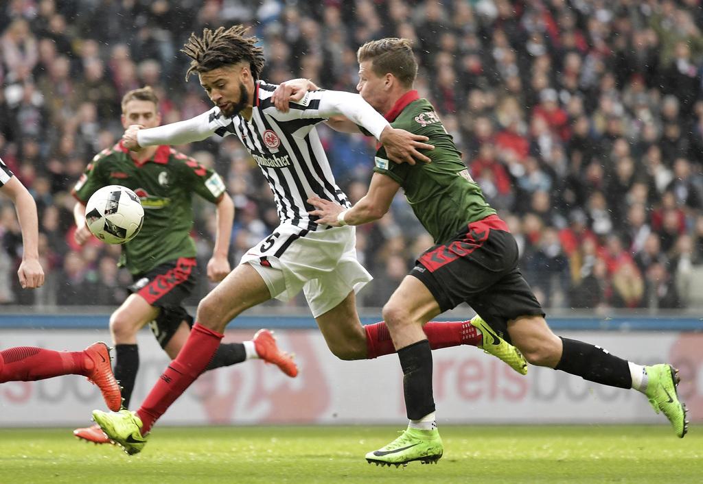 Frankfurt's Michael Hector, center, and Freiburg's Florian Niederlechner, right, challenge for the ball  during the Bundesliga soccer m...