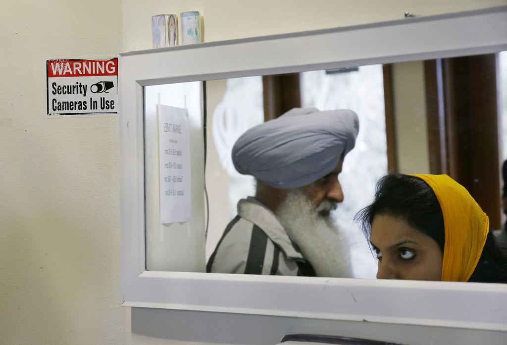 A sign notes the presence of security cameras at the Gurudwara Singh Sabha of Washington, a Sikh temple in Renton, Wash., Sunday, March...
