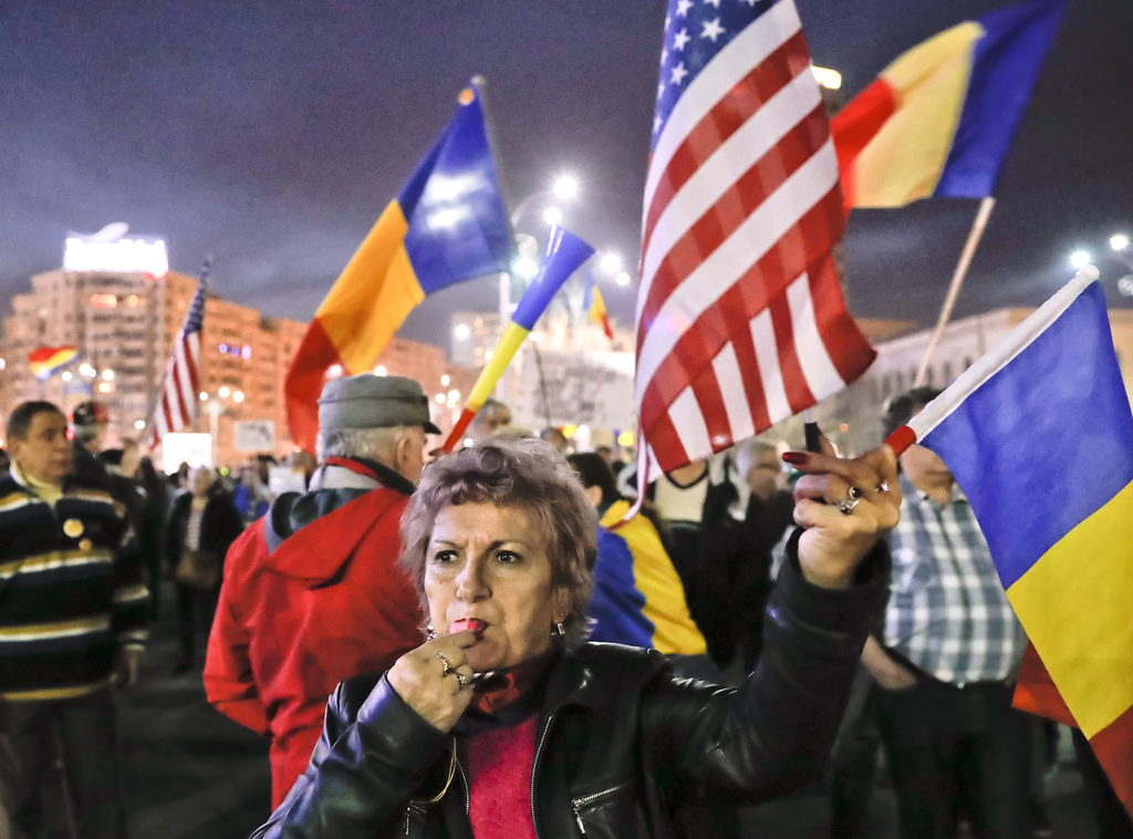 A protester blows a whistle as others shout anti-government slogans during a rally in Bucharest, Romania, Sunday, March 5, 2017. Thousa...
