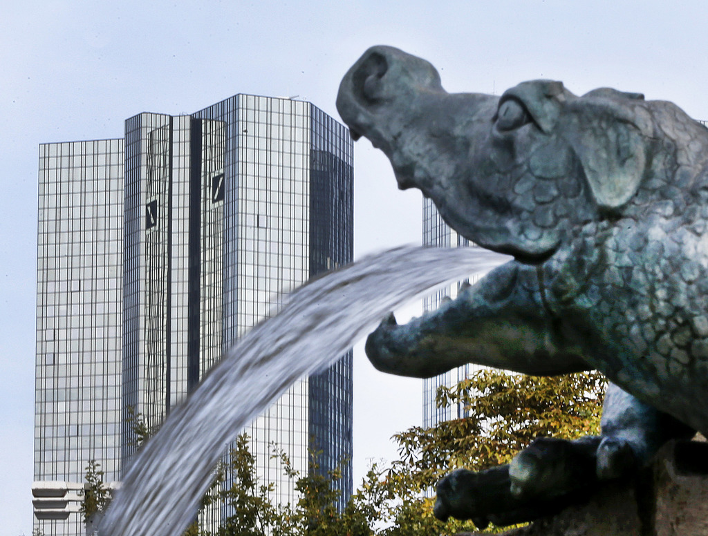 FILE - In this Oct. 11, 2016 file photo, water spills out of a small dragon sculpture on a fountain with the headquarters of the Deutsc...