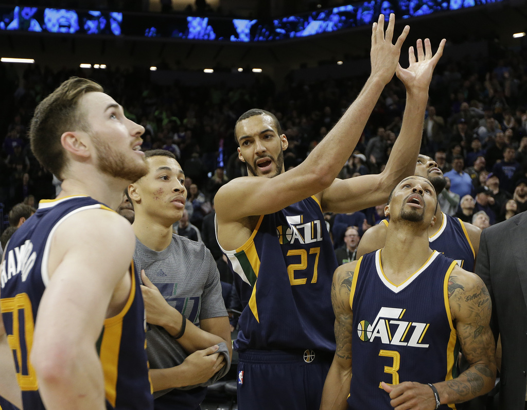As his teammates, Gordon Hayward, left, and George Hill, right, watch a replay on the scoreboard, Utah Jazz center Rudy Govbert, third ...