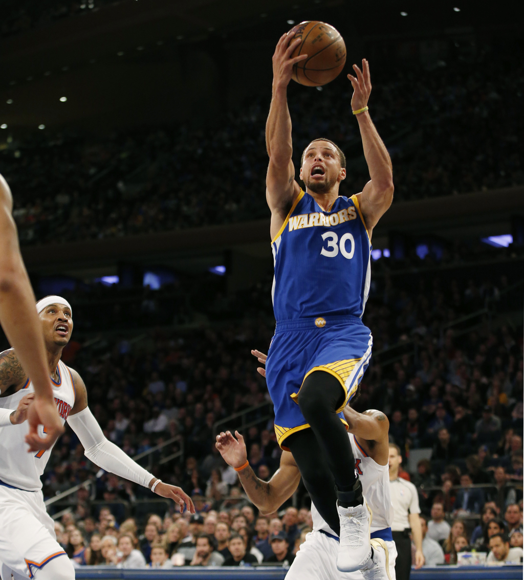 Golden State Warriors guard Stephen Curry (30) goes up for a layup as New York Knicks forward Carmelo Anthony, left, watches from the f...