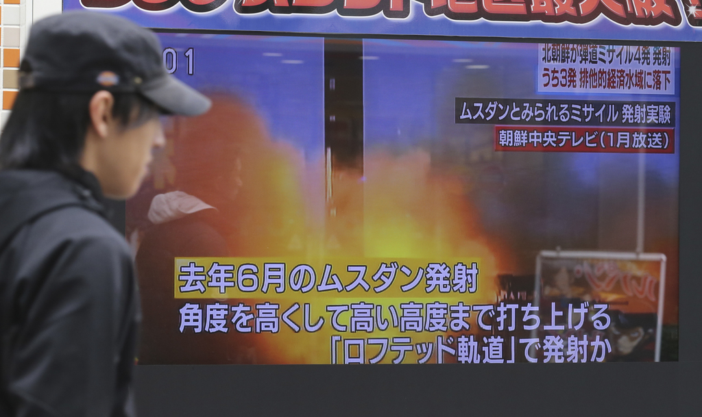 A man walks past a screen showing a TV news on North Korea's missile firing, in Tokyo, Monday, March 6, 2017.  North Korea on Monday fi...